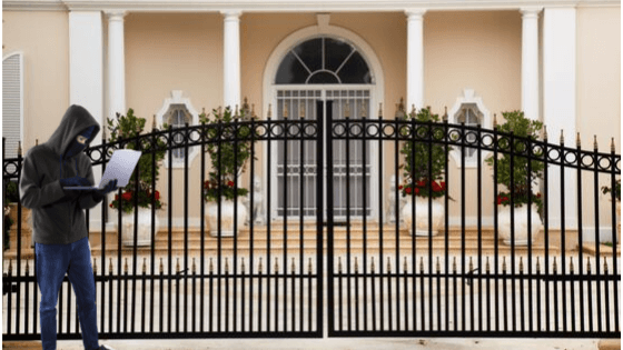 Hacker at the front gate of a luxury home