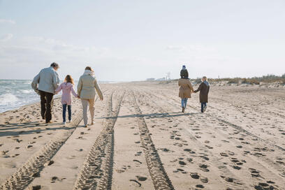 multigenerational family walking on beach rx