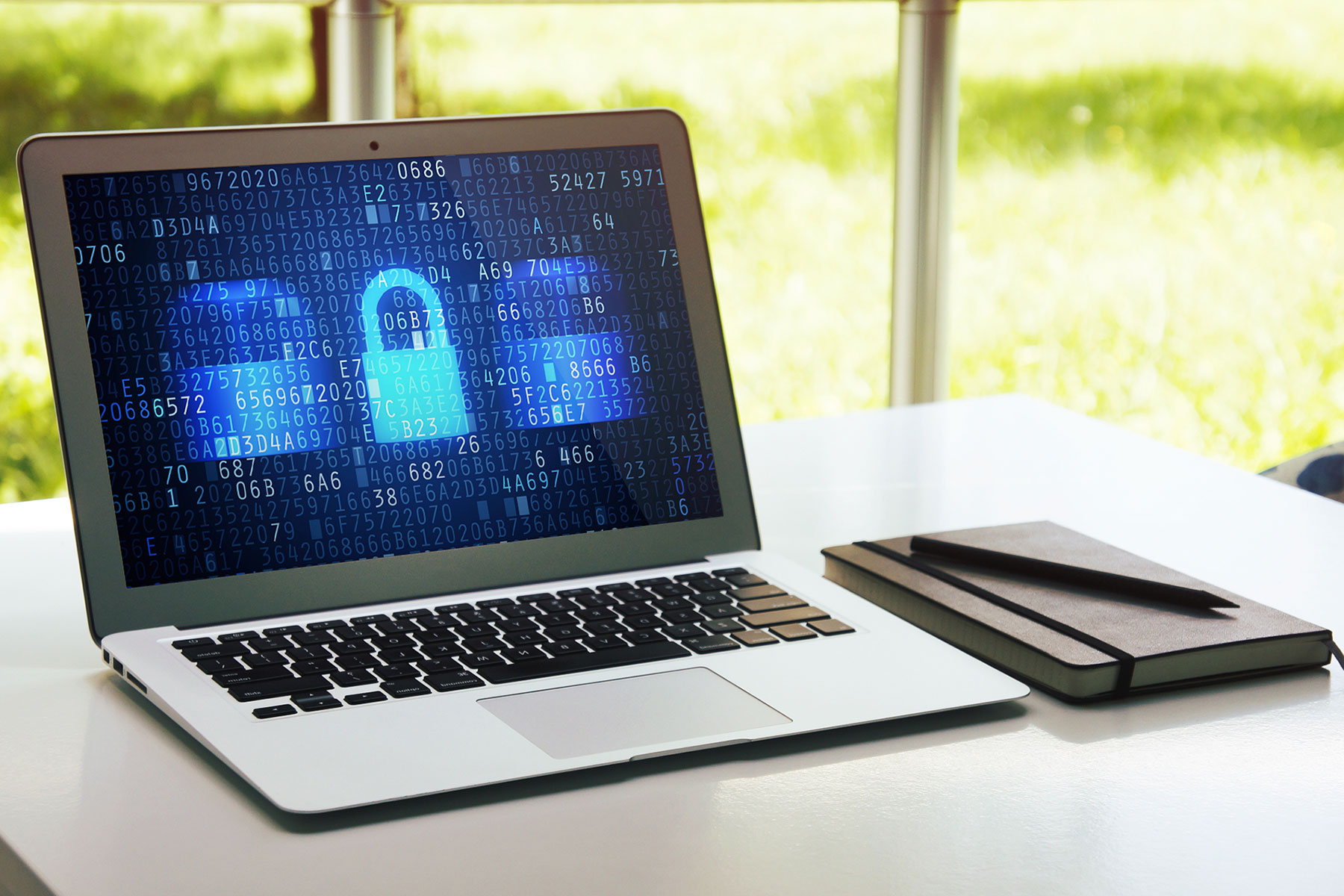 laptop on table with note pad cybersecurity at home