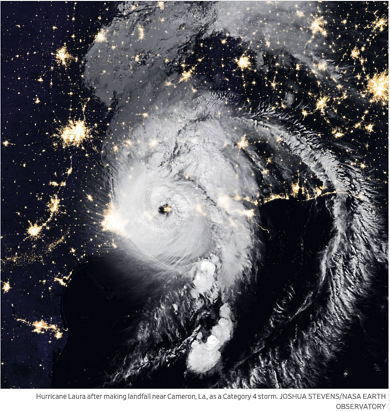 NASA satellite image of hurricane clouds over night time city lights.