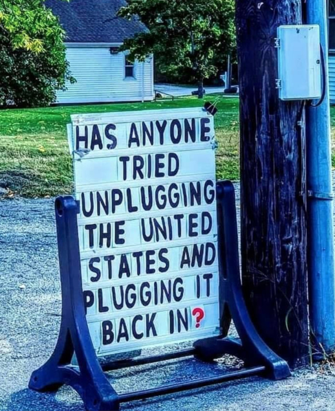 """sign on sidewalk says """"has anyone tried unplugging the U.S. and plugging it back in?"""""""
