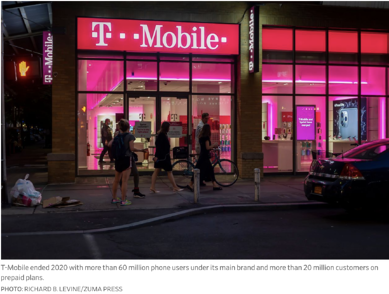 photo of T-Mobile store at night with red neon sign lights