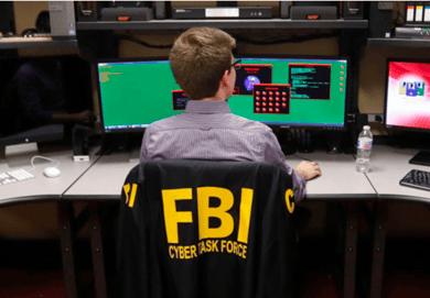 FBI agent sitting at computer screens