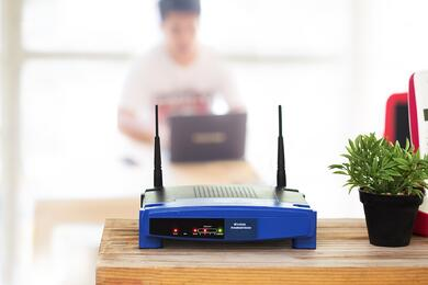blue wifi router green plant on wood desk man using laptop rx