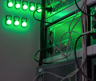 computers on racks with green lights mining crypto