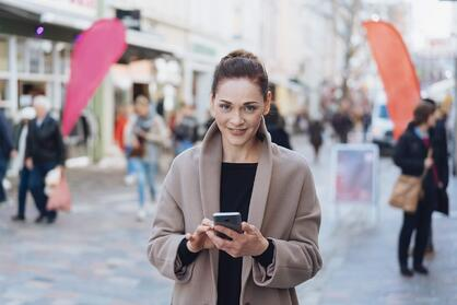 woman with phone using a VPN for privacy in public rx