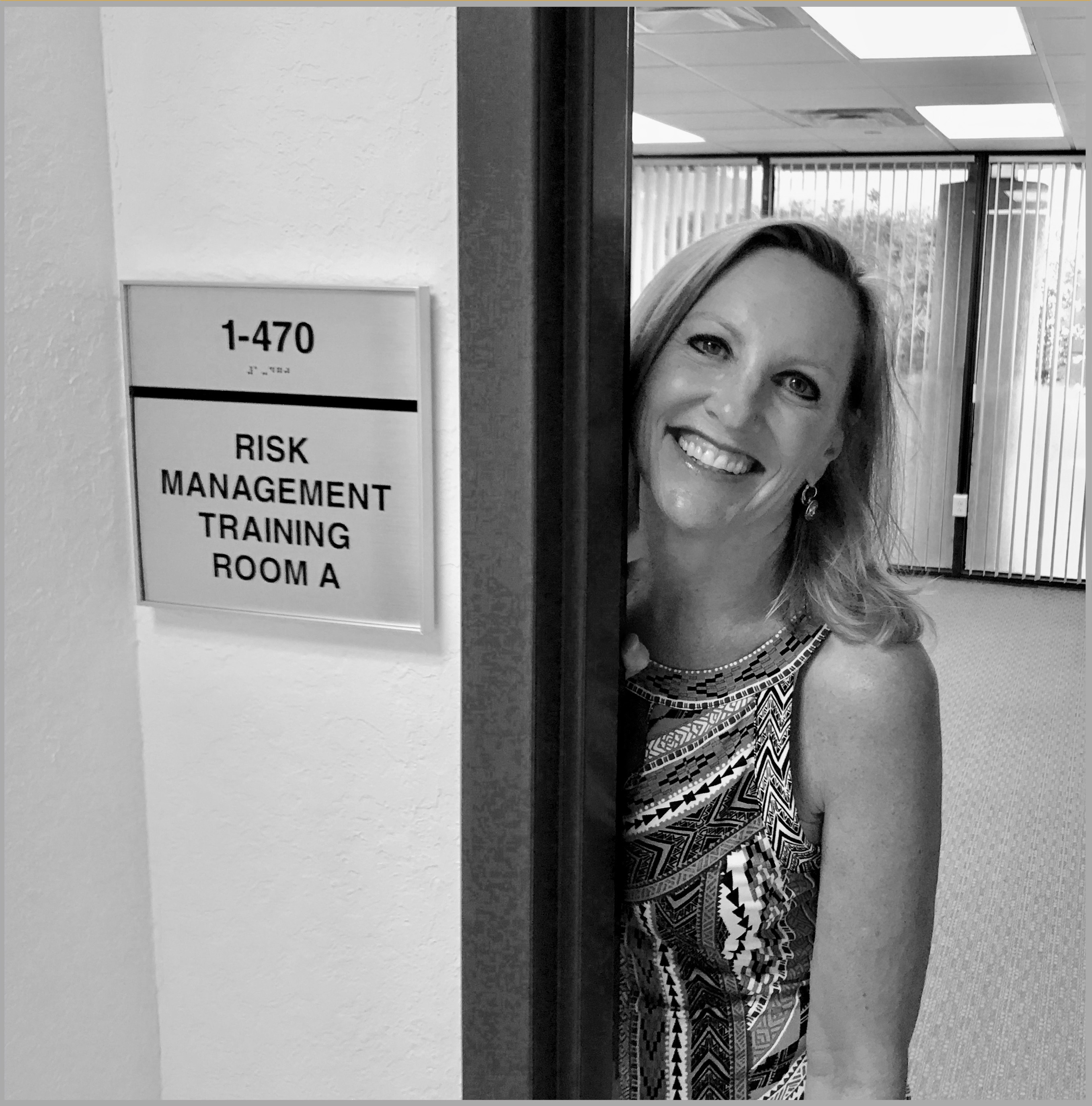 smiling woman at conference room door for cyber rick management training