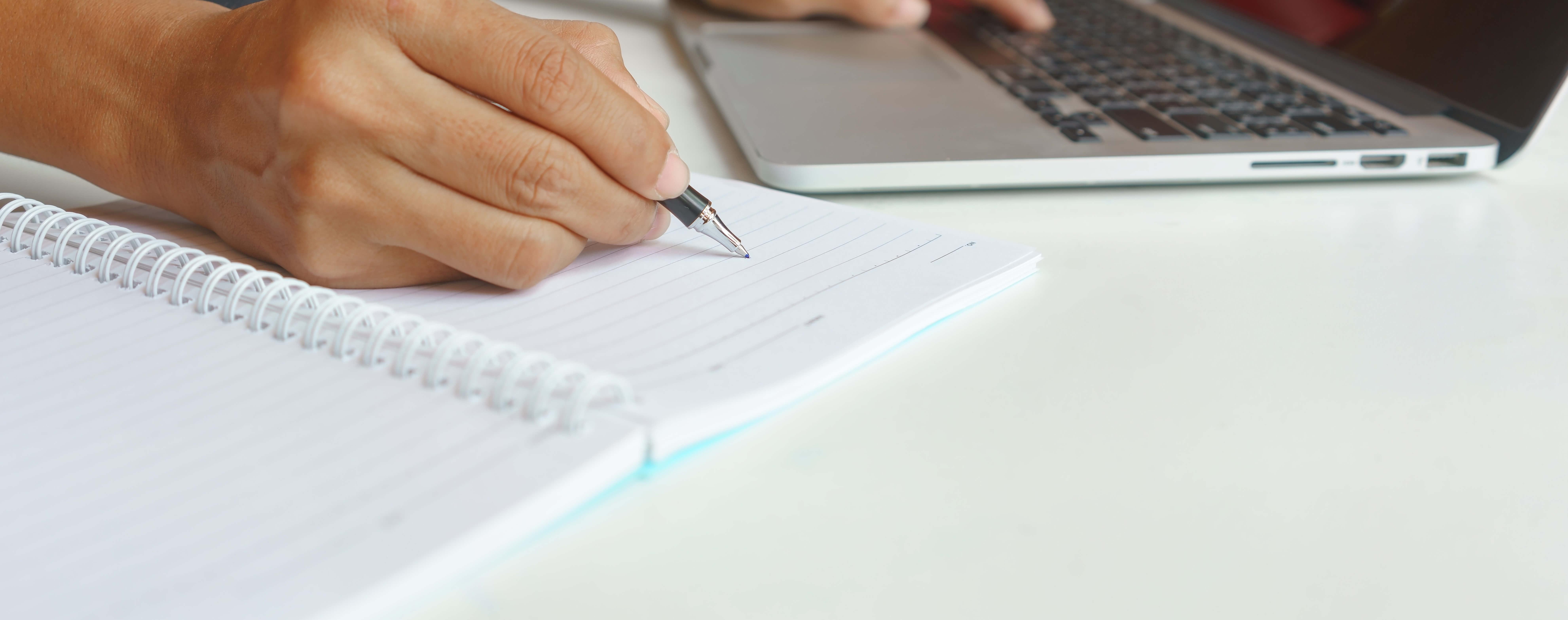 hand pen writing notebook laptop copy