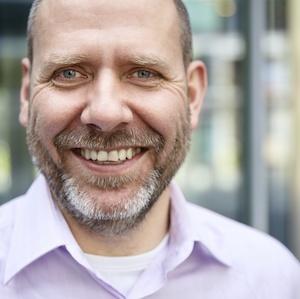 man beard smiling at camera pink shirt