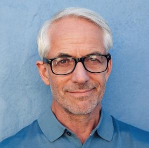 smiling man white hair blue shirt portrait